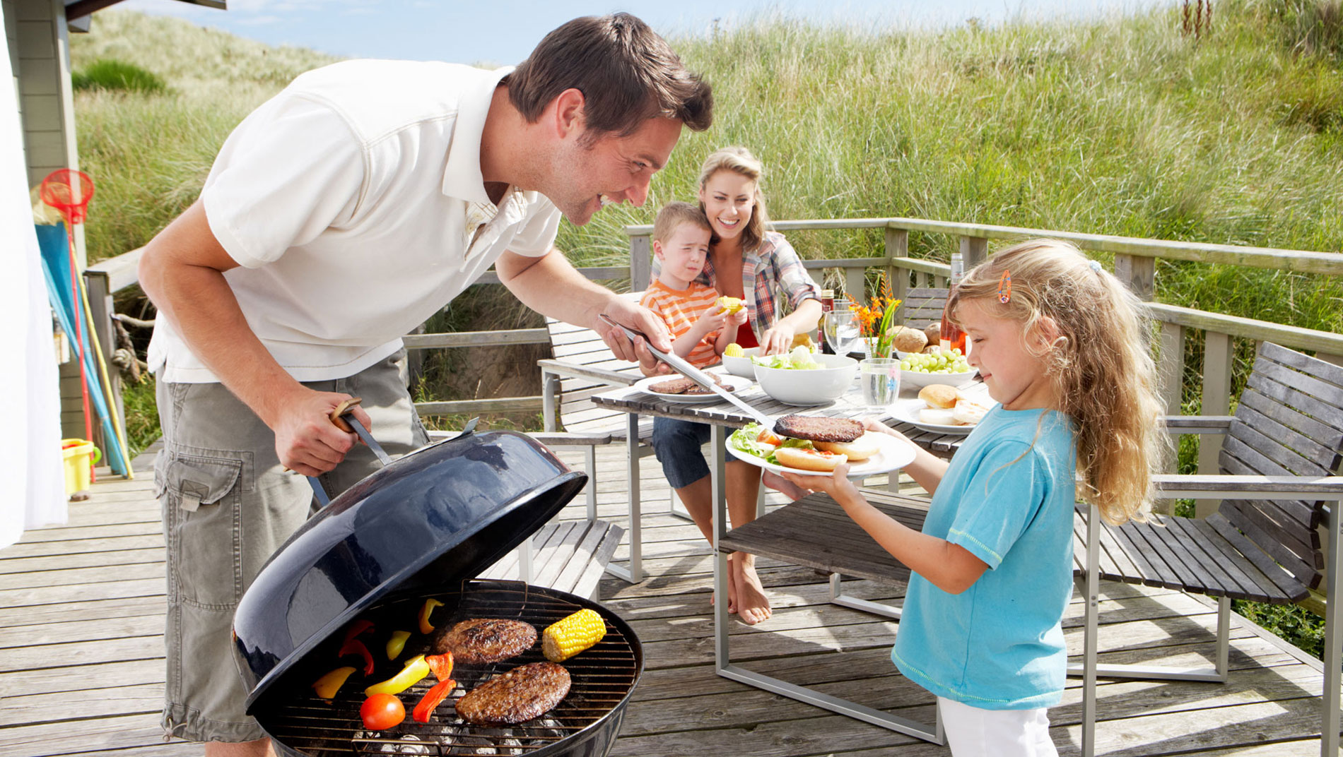 Happy dad having a BBQ with his children