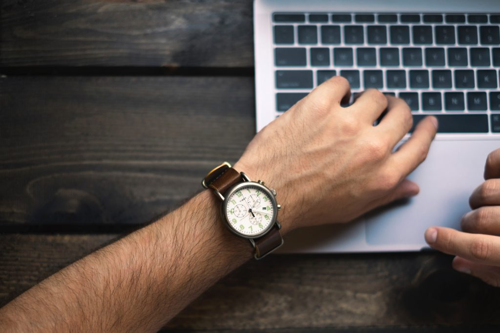 Man with watch on laptop