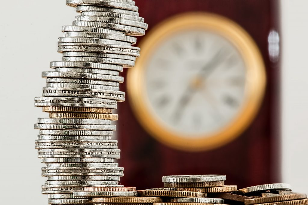 stack of silver and copper coins in front of clock